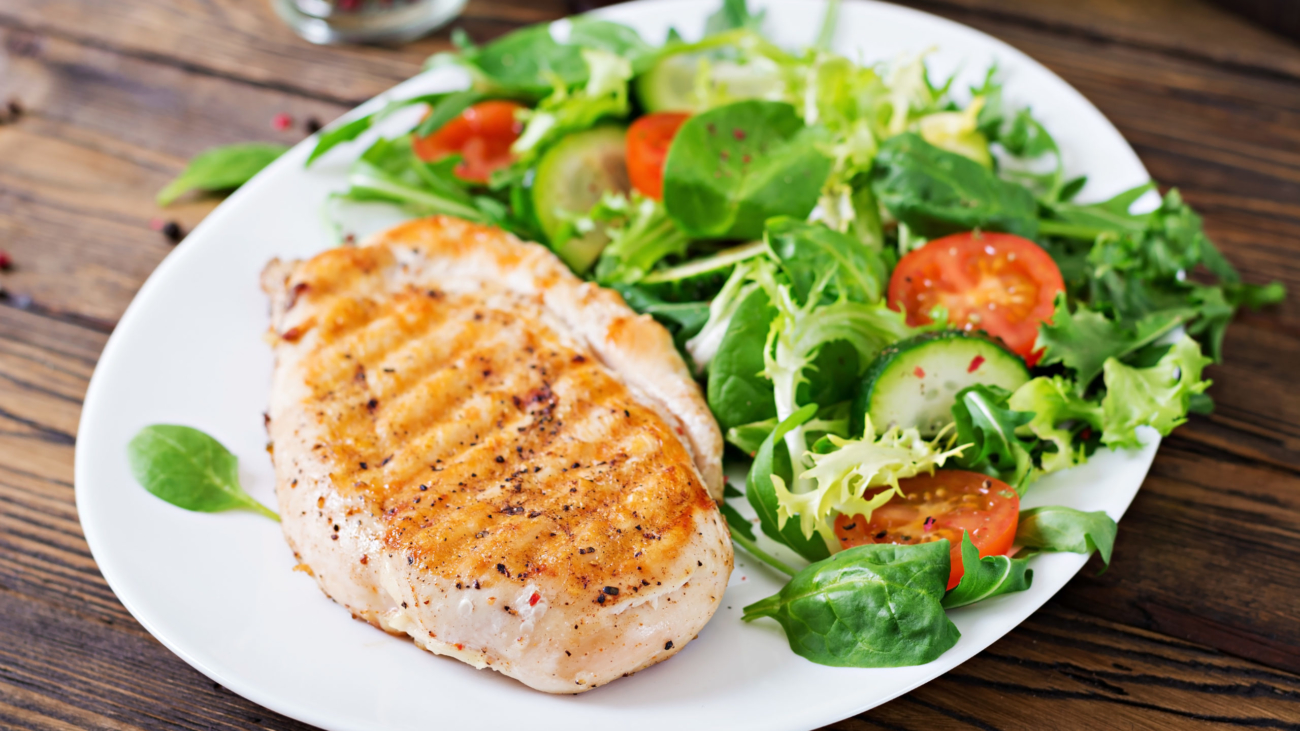 Grilled chicken breast and fresh vegetable salad - tomatoes, cucumbers and lettuce leaves. Chicken salad. Healthy food.