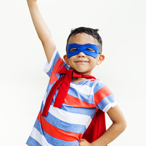Little boy playing superhero at the playground